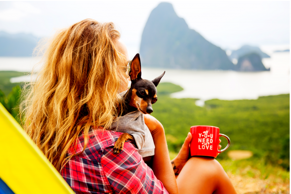 Woman and her dog outside drinking coffee, looking at the mountains and lake