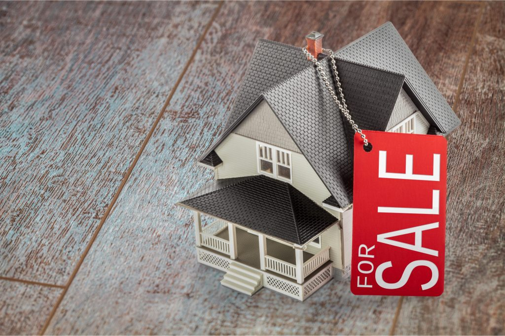 "Miniature house with a red ""For Sale"" tag on a wooden floor."